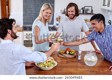 Cheers celebration drink friends at home party in kitchen - stock photo