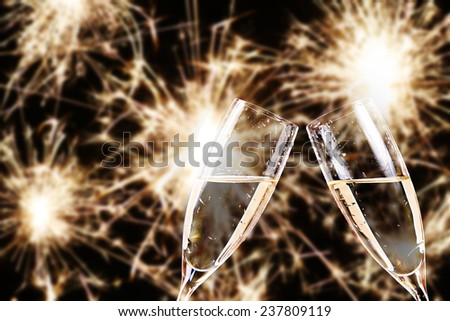 cheers. champagne glasses with fireworks in background - stock photo