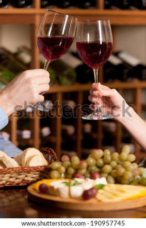 Cheers! Close up of people holding wine glasses at the restaurant  - stock photo