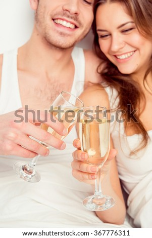 Cheers! Couple in love celebrate honeymoon with champagne on the bed - stock photo