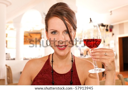 cheers - pretty woman with a glass of wine - stock photo