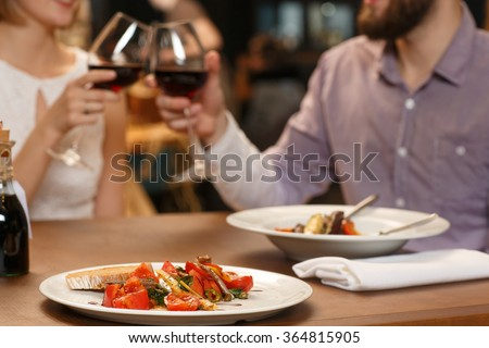 Cheers! Selective focus on delicious food on the restaurant table couple cheering with wine glasses on the background
