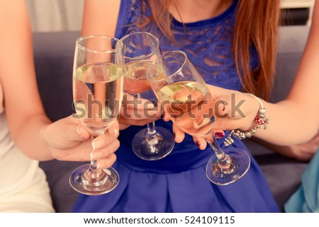 Cheers! Three girlfriends having party and drinking shampagne
