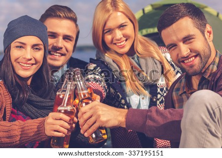 Cheers to friends! Four young happy people cheering with beer and smiling while sitting near the tent together - stock photo