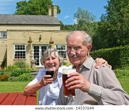 Cheers to over fifty years of married life. Couple in their 80s raise their glasses - stock photo