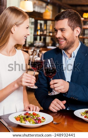 Cheers to us! Beautiful young loving couple toasting with red wine and smiling while sitting at the restaurant together - stock photo