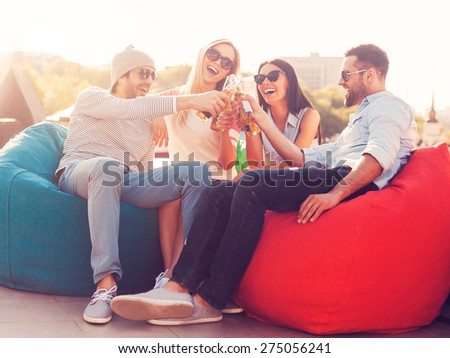 Cheers to us! Four young cheerful people cheering with beer and smiling while sitting at the bean bags on the roof of the building - stock photo