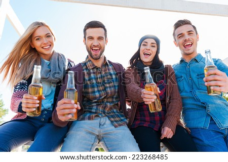 Cheers to you! Low angle view of young happy people cheering with beer and smiling while bonding to each other  - stock photo