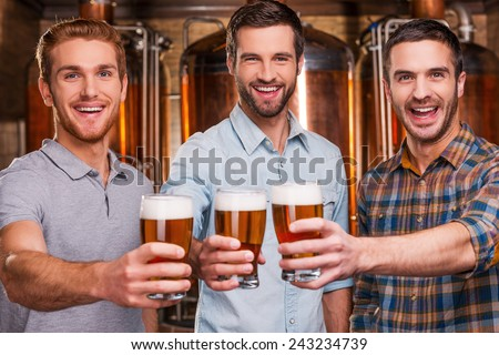 Cheers to you! Three cheerful young men in casual wear stretching out glasses with beer and smiling while standing in front of metal containers - stock photo