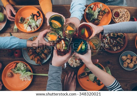 Cheers! Top view of people cheering with drinks while sitting at the rustic dining table - stock photo