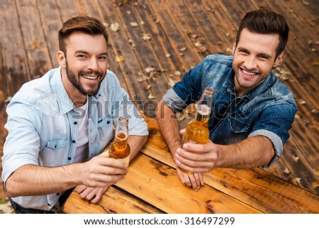 Cheers! Top view of two joyful young men stretching out bottles with beer and looking at camera while standing outdoors  - stock photo