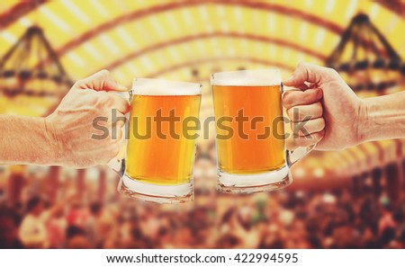 cheers, two glass beer mugs in hands - stock photo