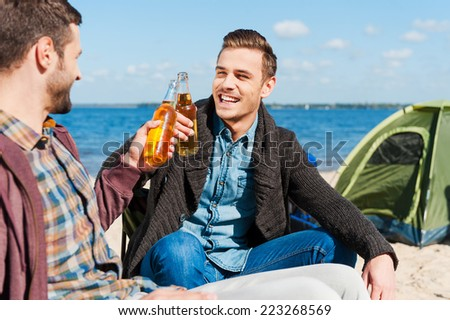 Cheers! Two happy men cheering with beer and smiling while sitting near the tent together  - stock photo