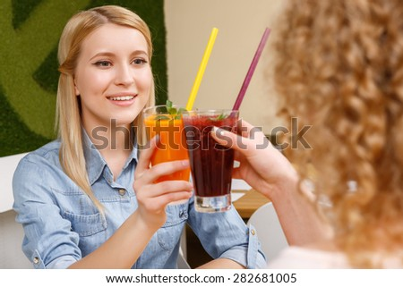 Cheers. Two young pretty girls sitting in cafe and clinking glasses with cocktails  - stock photo