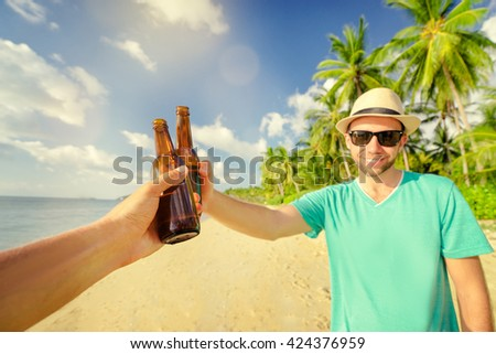 Cheers! Welcome to the beach party. Young smiling man drinking beer with friend on the sea shore. - stock photo