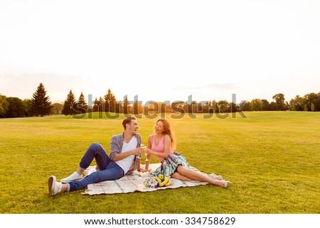 Cheers! Young man and woman at picnic - stock photo