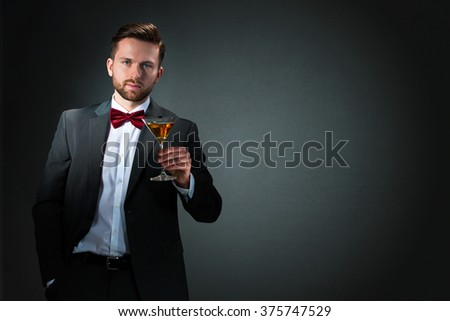 Cheers-Young man holding a tall cocktail glass on dark grey background
