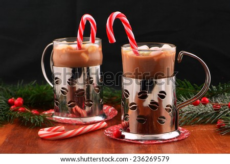 Cheery Christmas mugs of hot chocolate with mini marshmallows and peppermint candy canes on dark background with room for your text - stock photo