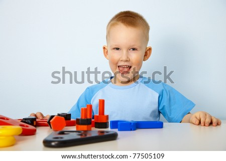 Cheery little boy playing with toys on the table - stock photo