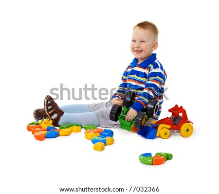 Cheery little boy sitting among colorful toys on the floor - stock photo