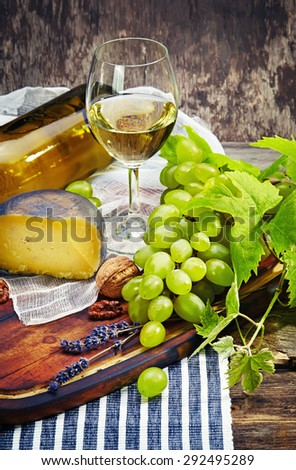 Cheese, a bottle of wine with grape, walnut and fig on old wooden cutting board