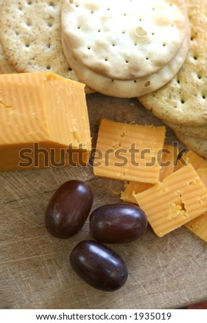 Cheese and biscuits served on wooden tray with red seedless grapes. - stock photo