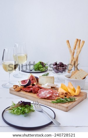 Cheese and charcuterie pairing, chorizo salami, served with fresh fruit rockmelon, fig with olives, salad and white wine - stock photo