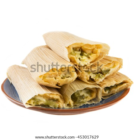 Cheese and chili tamales on plate and isolated on white background, view from eye level.