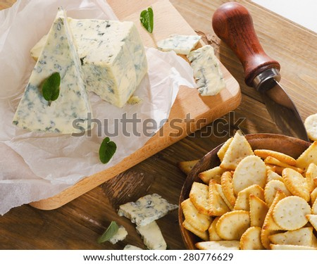 Cheese and crackers on a  wooden table . Selective focus - stock photo