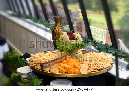 Cheese and Crackers served at a catered affair with greenery in the background