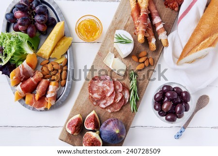 Cheese and cured meat charcuterie selection cheddar, gruyere, salami, chorizo, prosciutto wrapped bread sticks with fresh fig, rockmelon, almonds - stock photo