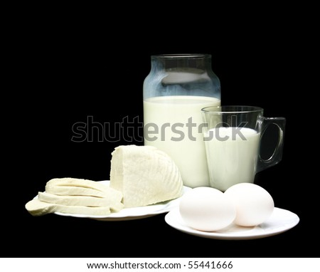 Cheese and eggs on front of milk, over black