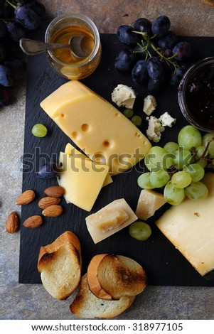 cheese and fruits on slate, food above