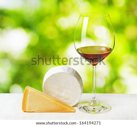 Cheese and glass of wine on nature background. - stock photo