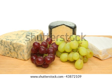 Cheese and grapes on a wooden board - stock photo