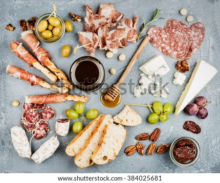 Cheese and meat appetizer selection or wine snack set. Variety of  cheese, salami, prosciutto, bread sticks, baguette, honey, grapes, olives, sun-dried tomatoes and pecan nuts over grey backdrop - stock photo