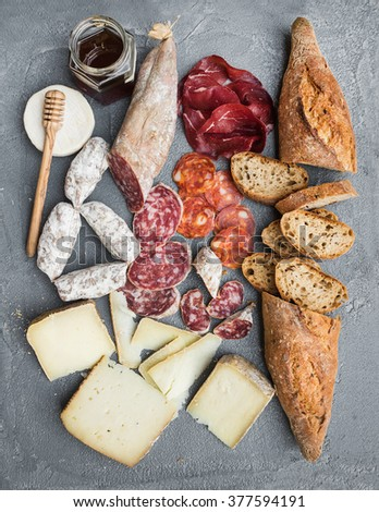 Cheese and meat appetizer selection or wine snack set. Variety of italian cheese, salami, bresaola, baguette and honey on over grey concrete backdrop, top view, vertical - stock photo