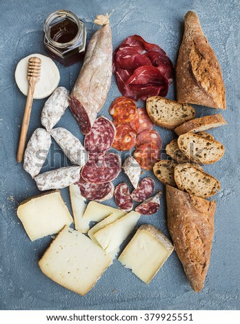 Cheese and meat appetizer selection or wine snack set. Variety of italian cheese, salami, bresaola, baguette and honey on over grey-blue concrete backdrop, top view - stock photo