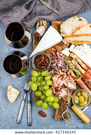 Cheese and meat appetizer selection. Prosciutto di Parma, salami, bread sticks, baguette slices, olives, sun-dried tomatoes, grapes and nutson rustic wooden board, two glasses of red wine over grey - stock photo