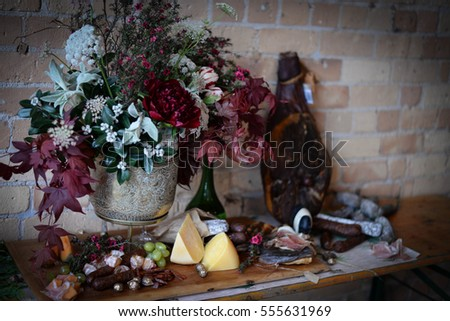 Cheese and Meat on Wooden Table with flowers decoration