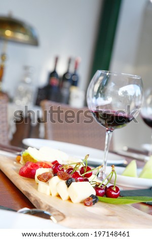Cheese and nuts on cutting board, wine glasses./Dinner table. - stock photo