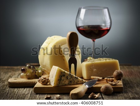 Cheese and red wine on wooden board. - stock photo