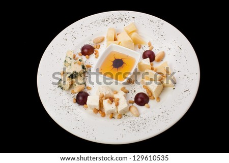 Cheese and salami platter with vegetable on a black background - stock photo