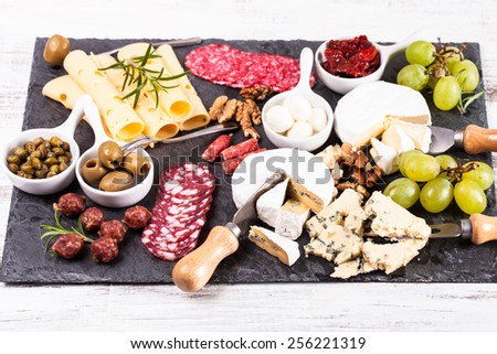 Cheese and salami with olives and nuts on a slate board - stock photo