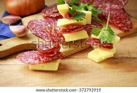 cheese and sausage slices for an appetizer - stock photo