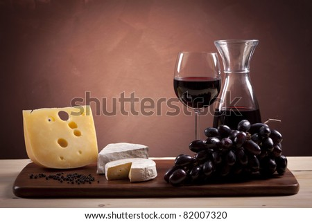 Cheese and wine composition on wooden table - stock photo