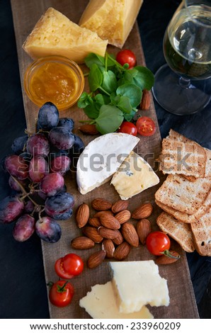 Cheese and wine tasting platter with variety of cheeses, jam, grapes, raw almonds, cherry tomatoes, crackers, luxurious party entertaining gourmet food - stock photo