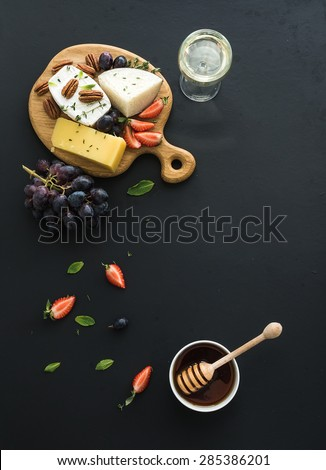 Cheese appetizer selection or whine snack set. Variety of cheese, grapes, pecan nuts, strawberry and honey on round wooden board over black backdrop, top view, copy space - stock photo