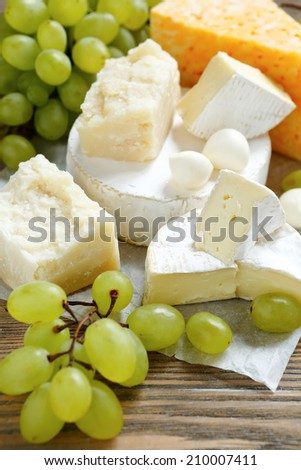 Cheese Assortment with grapes on a wooden background, food - stock photo