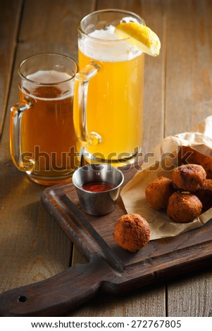 Cheese balls with spicy sauce in paper envelope on a dark wooden board and two glasses of beer with lemon - stock photo